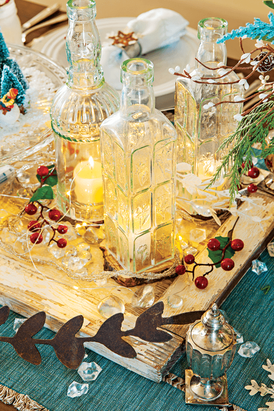 The centerpiece of the dining room table is layered with different colors and textures, including a blue table running, a rustic door-turned makeshift tray and repurposed bottles to serve as candle holders.