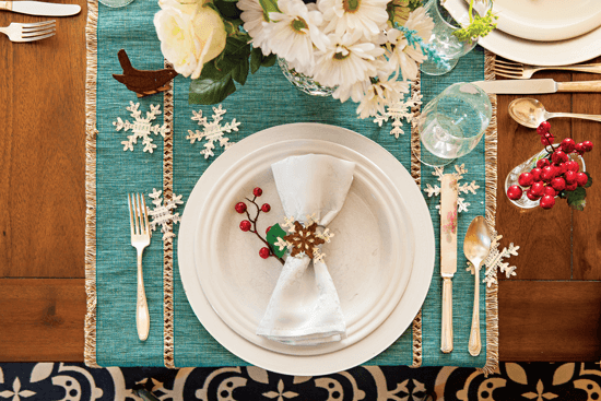 Snowflakes cut from old sheet music add a delightful layer of texture to the table.