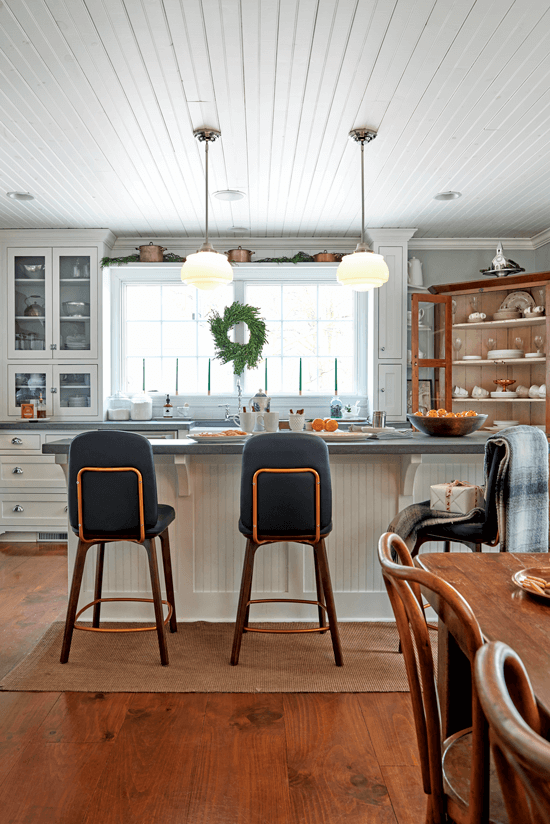 Navy barstools and a plaid blanket are placed at the island of this all-white kitchen, giving the light and bright space a cozy feel.
