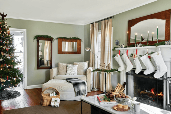 Cozy living room decorated with a Christmas tree and five white stockings hanging above the mantel. Live greenery is used to add pops of color and festivity.