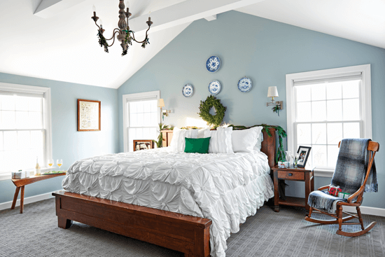 Light blue master bedroom accented with pops of fresh greenery and rustic boxwood.