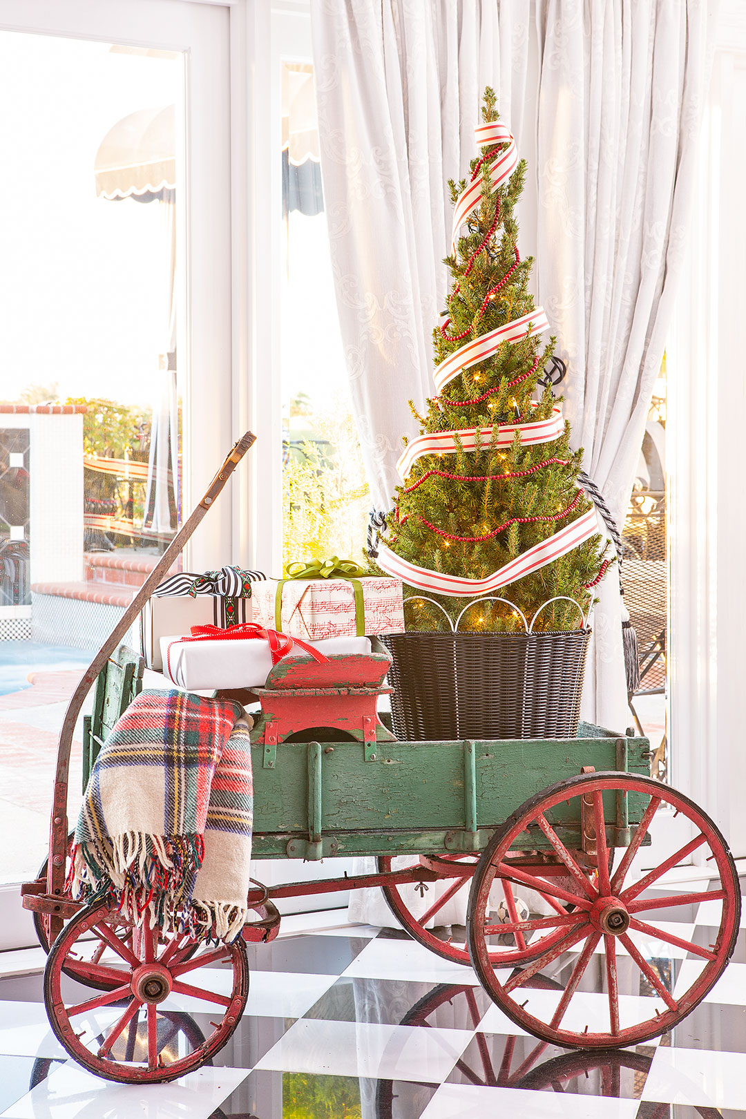 An antique, green wagon with a small tree, wrapped gifts and a tartan blanket in it