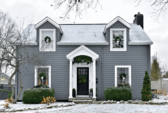 The snowy, grey exterior of this 1940 Cape Cod home is adorned with green wreaths and Granny Smith apples.