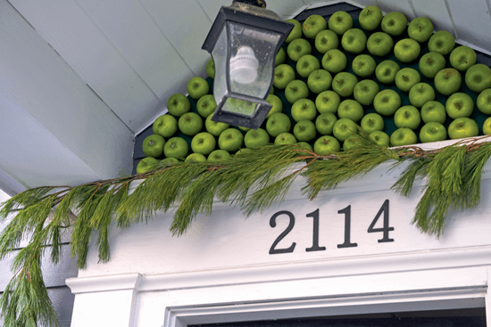 The space above the front door is decorated with textured greenery and green apples.