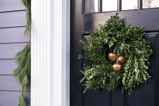 The dark front door of this home allows the green wreath to pop.