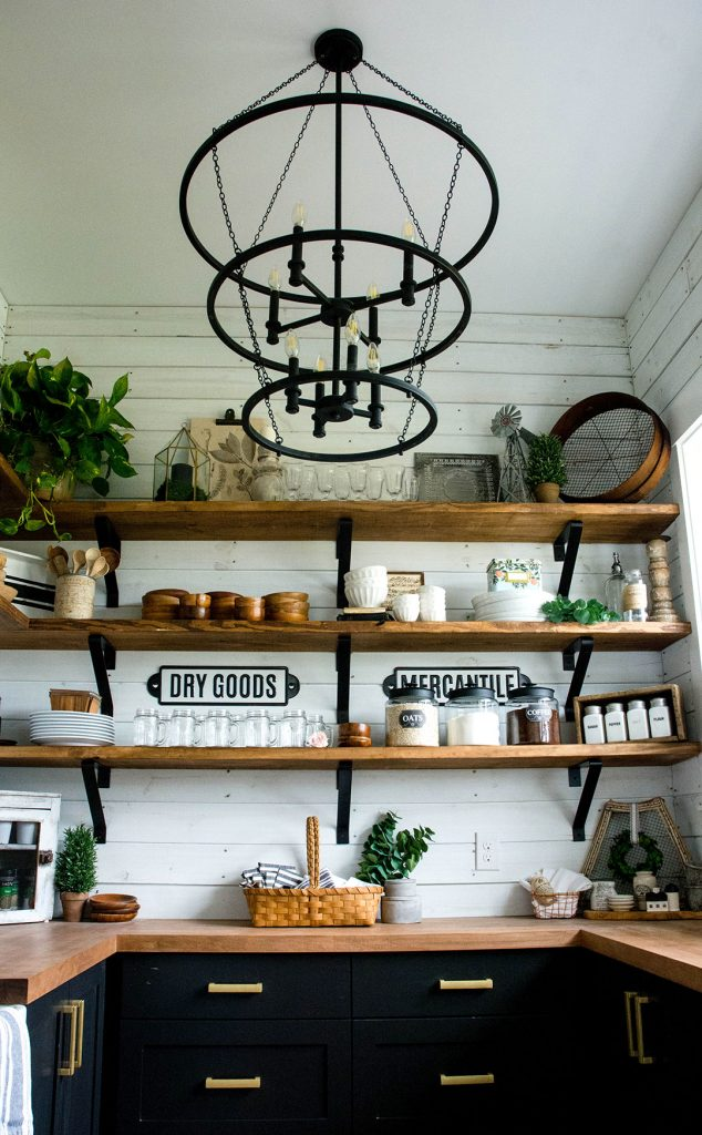 Farmhouse pantry with open shelves, black cabinetry and butcher block counters.