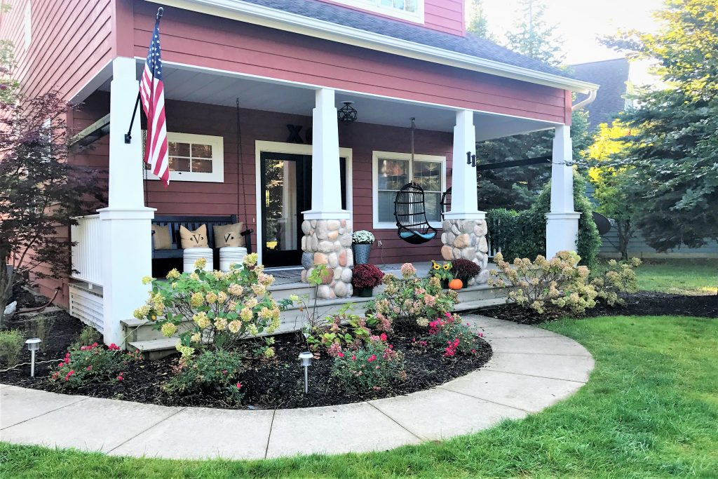 Front of the Victory Farms house with a meandering sidewalk and beautiful flowers.