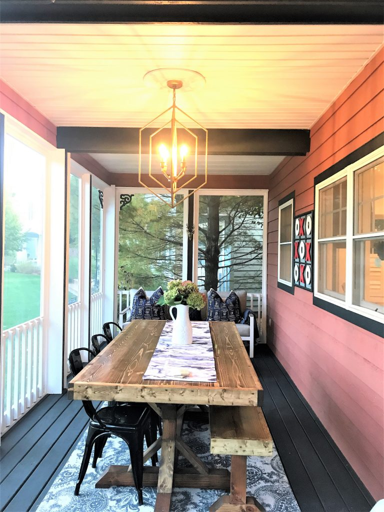 The updated cozy screened in porch from the Victory Farms project features a long farmhouse table and bench.