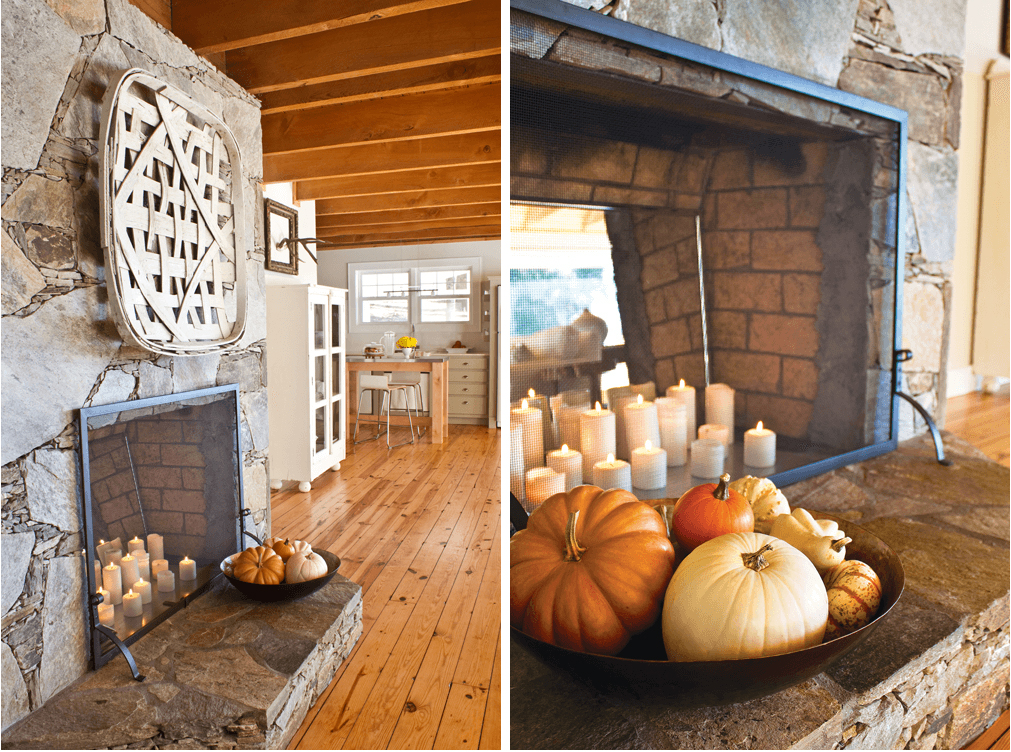 stone fireplace decorated for fall with pumpkins, candles and a tobacco basket