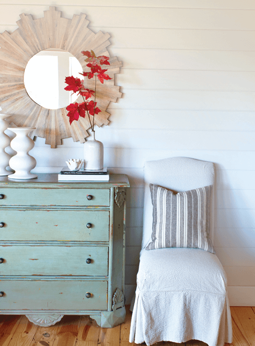 covered accent chair with decorative throw pillow alongside a distressed chest of drawers