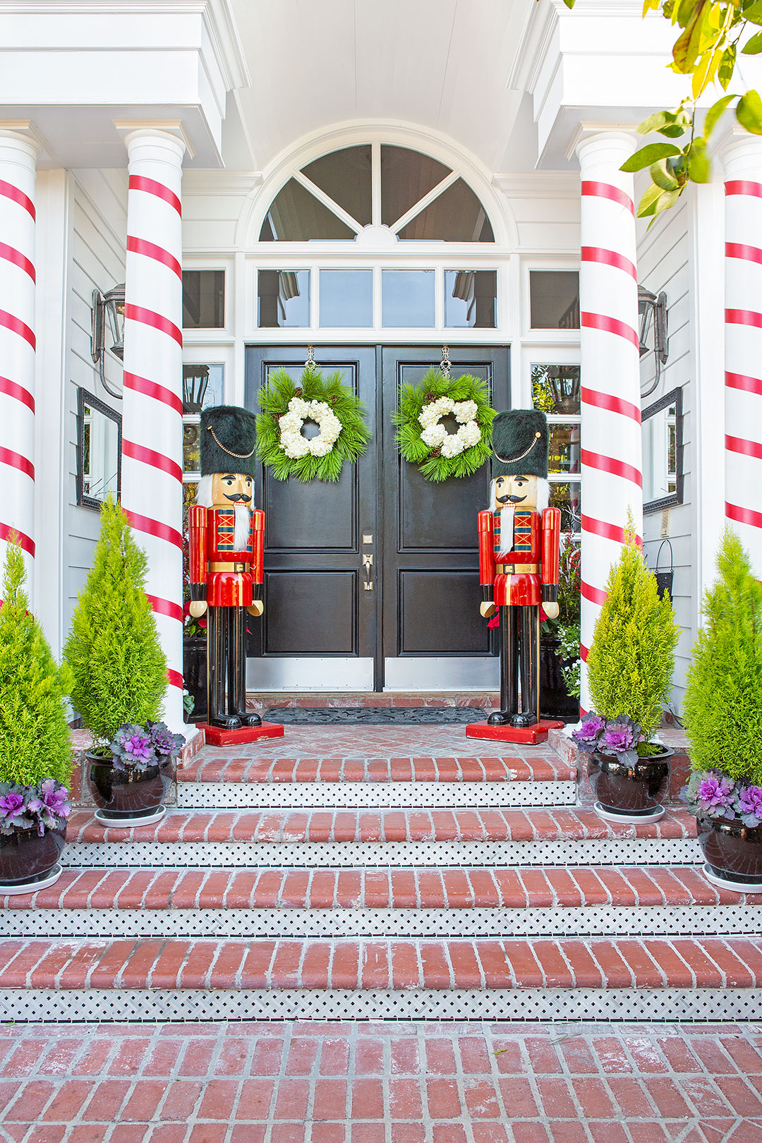 Christmas porch decor with two giant nutcrackers, candy candy columns, and wreaths on the door