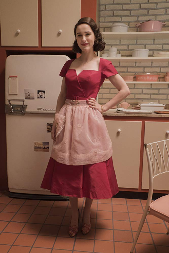 Midge Maisel played by the charming Rachel Brosnahan standing in her 1950s-inspired kitchen.