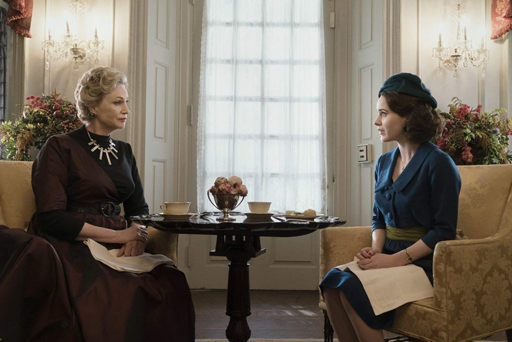 Mrs. Maisel sharing tea alongside a cast-member, both of whom are sitting in elegant patterned accent chairs.