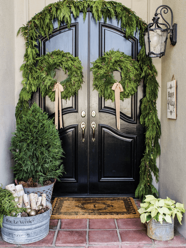 Fresh, natural greenery is the perfect front door decor with two wreaths and a garland over the door.