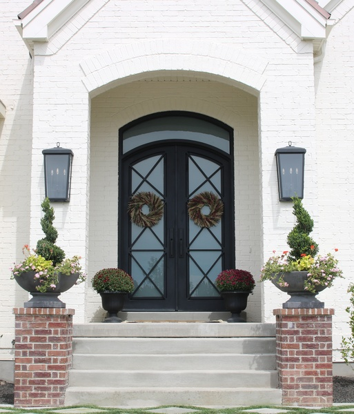 Capital Lighting's Donnelly Outdoor Lanterns flank the front arched door of this white brick home. Playing off the flat black finish on the steel doors, the lanterns feature a simple, traditional look that adds stately charm.