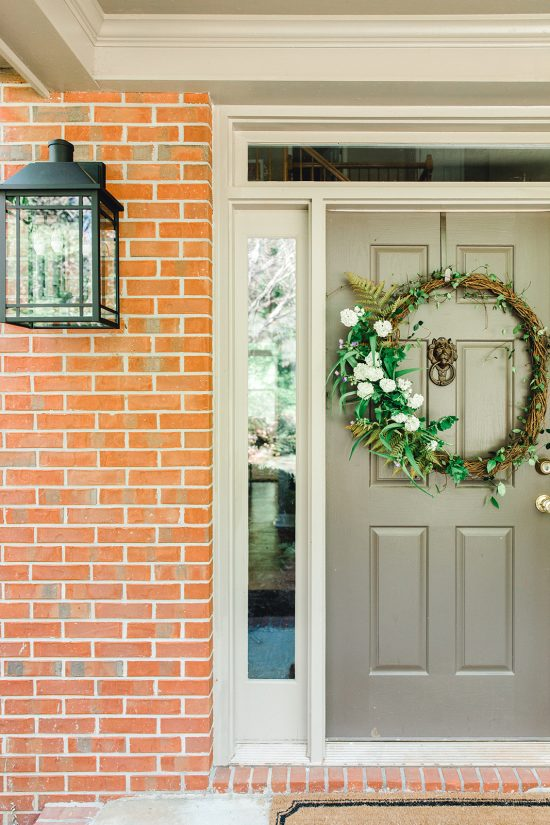 Front door close-up featuring a simple wreath and lantern from Capital Lighting's Braden Collection.