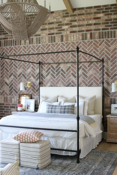 Master bedroom decorated with French country décor and a herringbone brick accent wall, featuring a beautifully beaded chandelier from Capital Lighting's Kayla Collection.