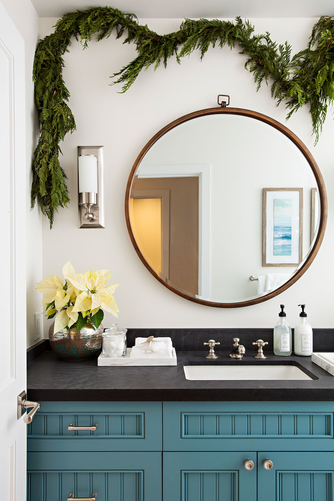 Natural greenery Christmas garland hung in the bathroom over a circular mirror.
