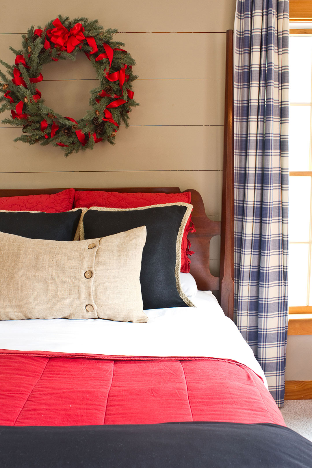 Gray shiplap wood paneled walls with wreath hanging over a guest bed for overnight holiday guests.