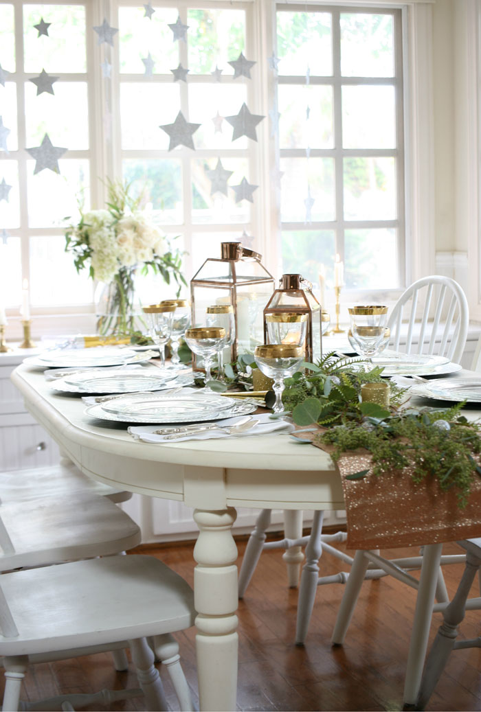 New Year's Eve table decor with lanterns, greens and a white table