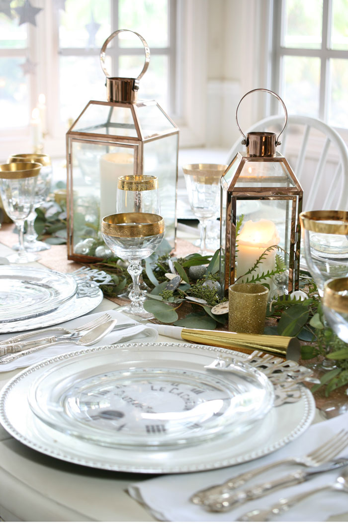 Copper lanterns, gold-rimmed champagne glasses, silver chargers and a rose gold table runner harmonize perfectly on this New Year's Eve tablescape.