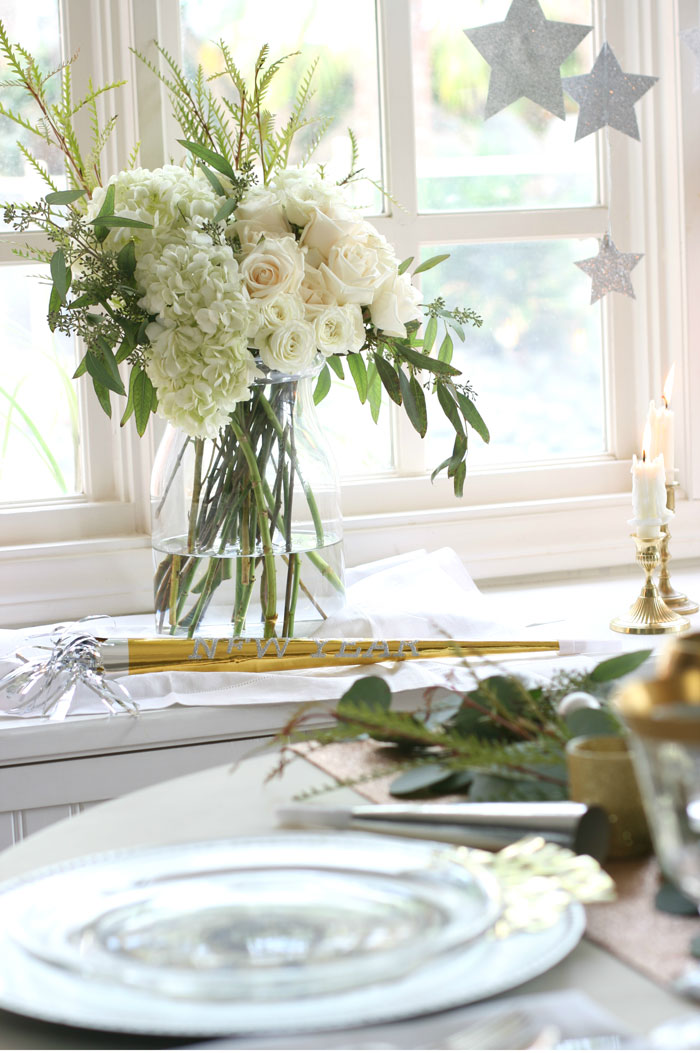 Elegant white roses and hydrangeas, glittery stars and brass candlesticks are simple elements that work perfectly with the tablescape.