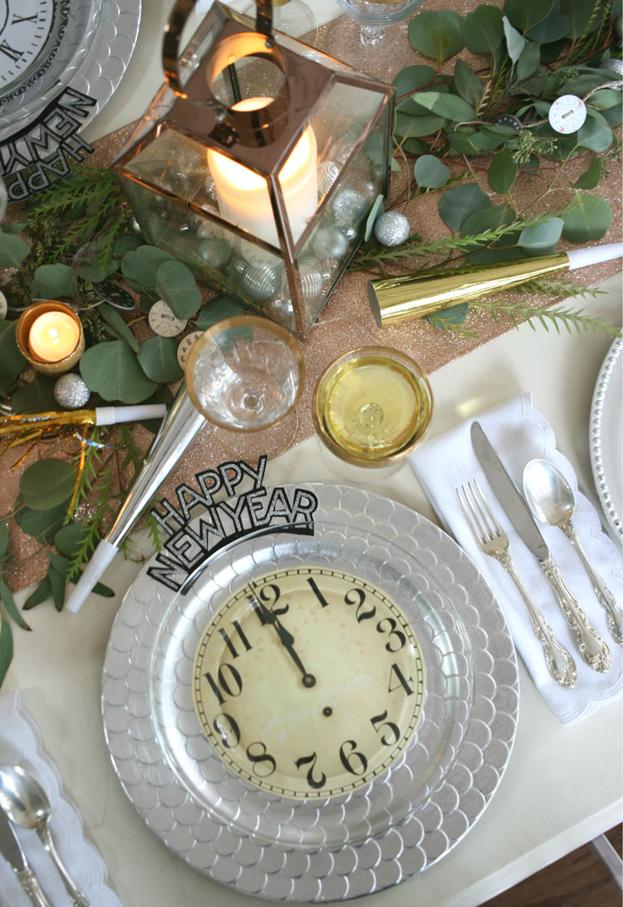 5853 Setting a table with a mix of our favorite metals, includes gold rimmed champagne glasses, silver chargers, copper lanterns and a glittery rose gold table runner. These fun clock plates are a cinch to make!