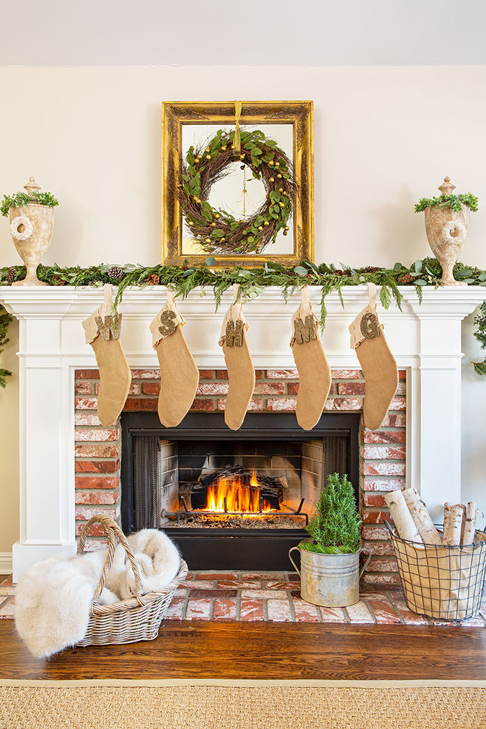 The mantel at Maison de Cinq is surrounded by natural greenery and decorated with a neutral color palette