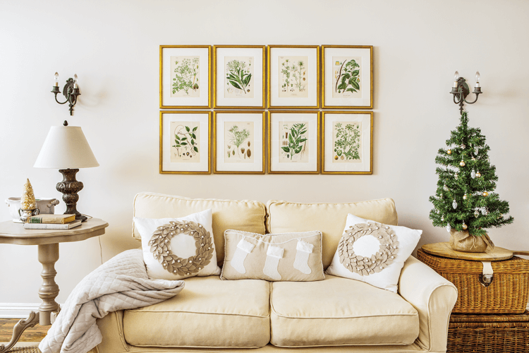 Vintage botanical prints hang over a love seat decorated with festive throw pillows