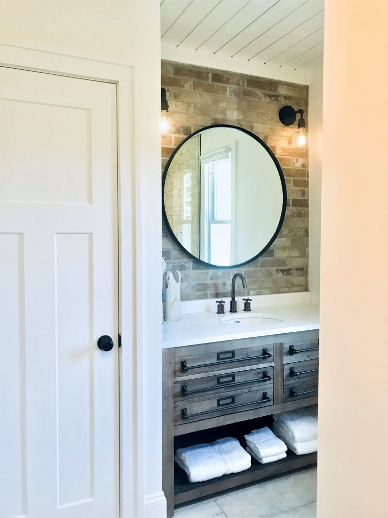 Bathroom remodel using brick and a reclaimed wood vanity.