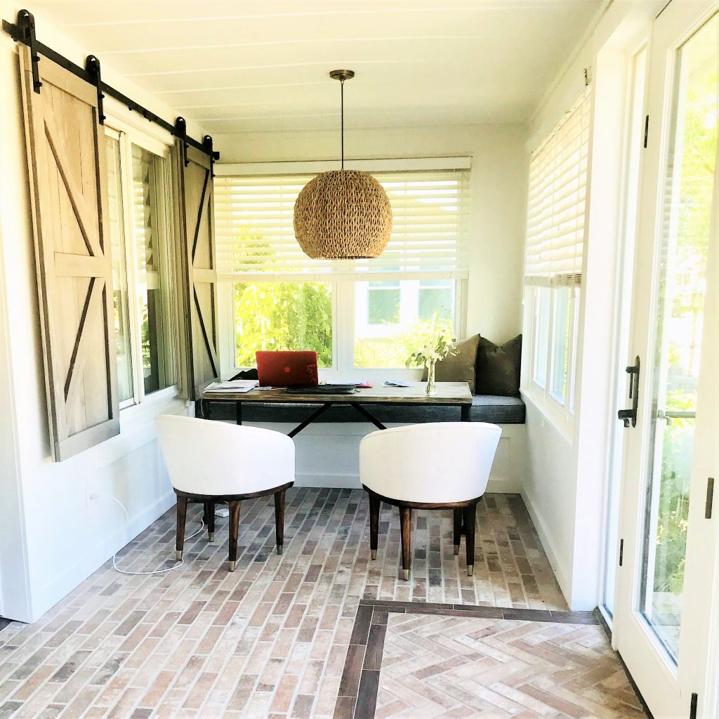 Remodeled sunroom with brick-look tile flooring and a simple but efficient and stylish office nook.