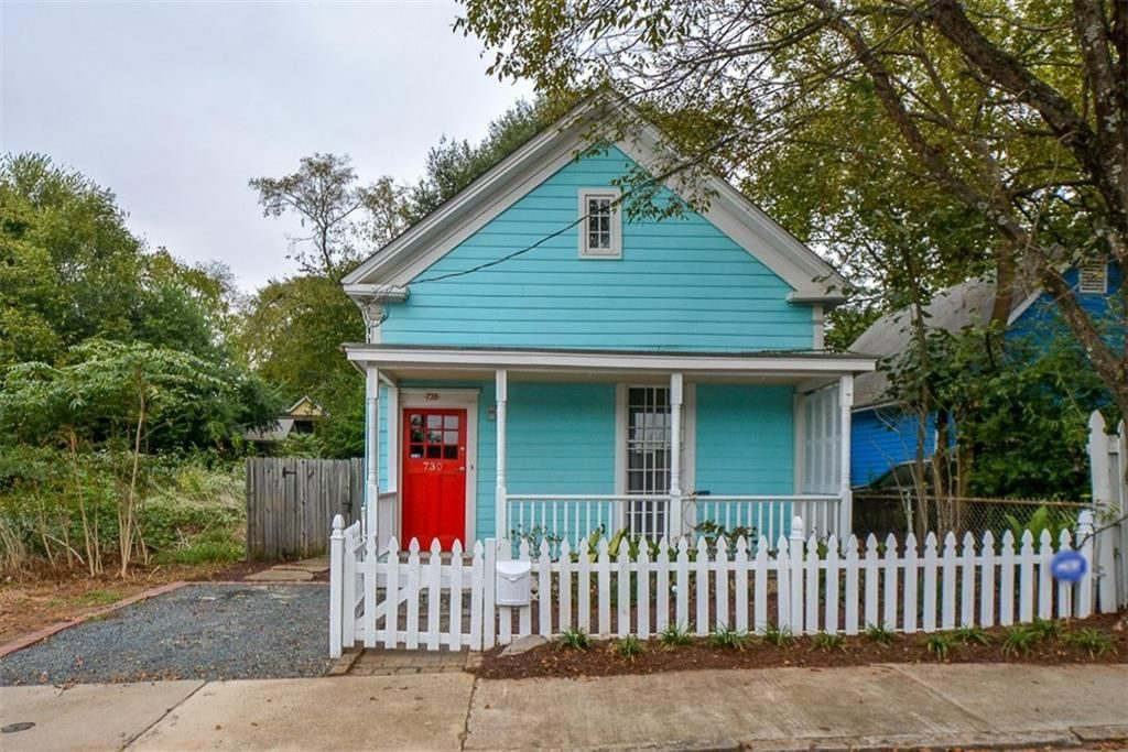 Colorful quaint cottage in Atlanta with white picket fence.