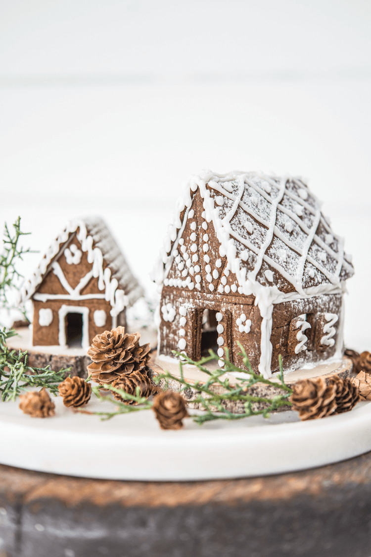 Two small gingerbread houses with white frosting details surrounded by pinecones and greenery.