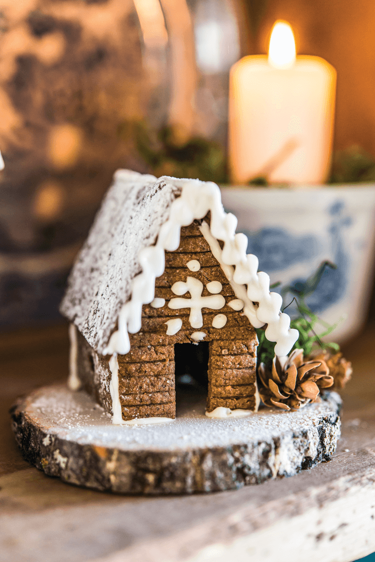 Small gingerbread cabin placed on a wooden stump.