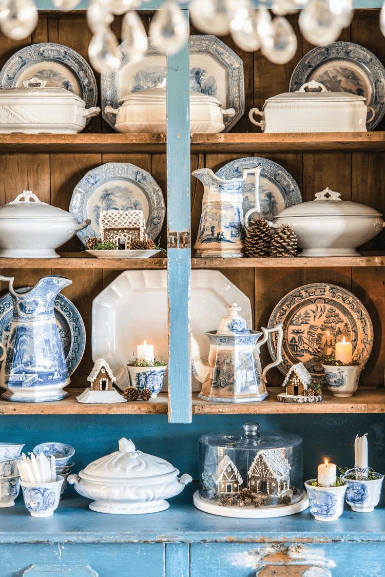 China cabinet with blue and white dishes and small Gingerbread Décor houses placed throughout.