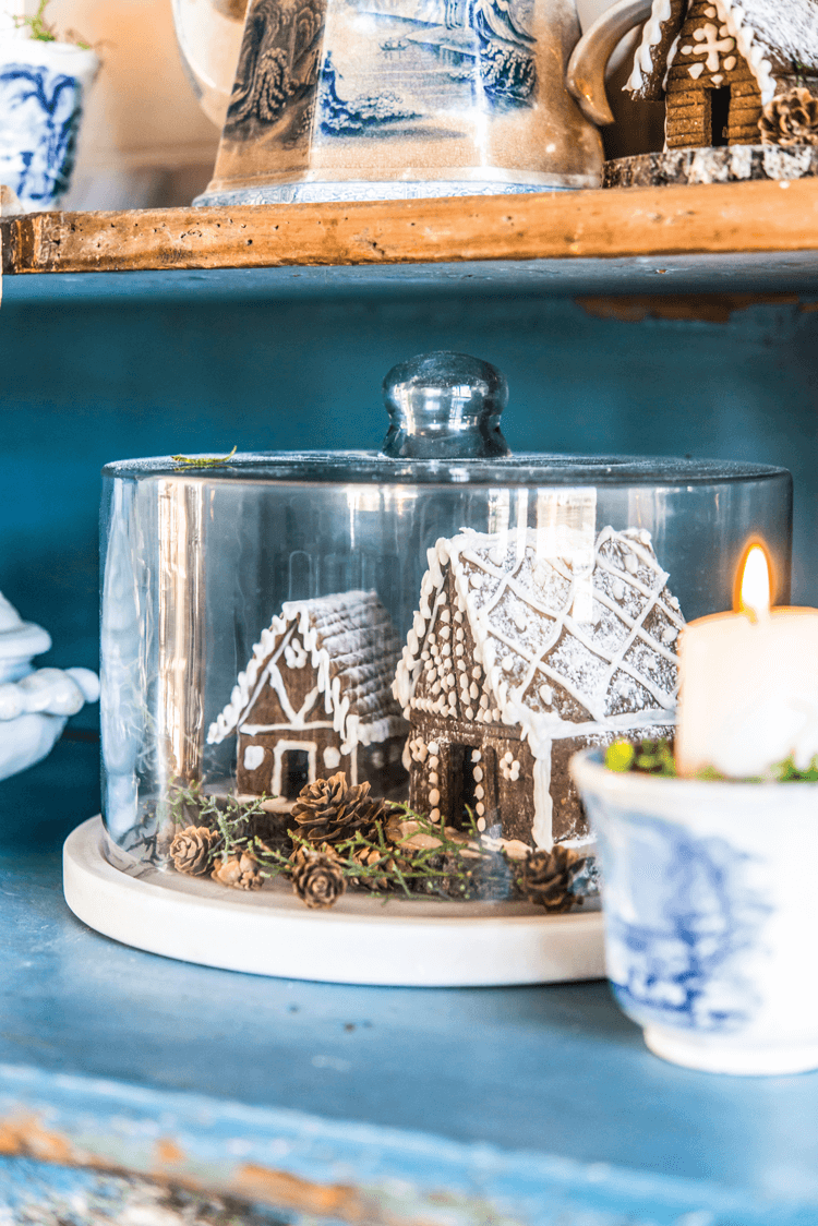 Small gingerbread village in display under a glass cake stand.