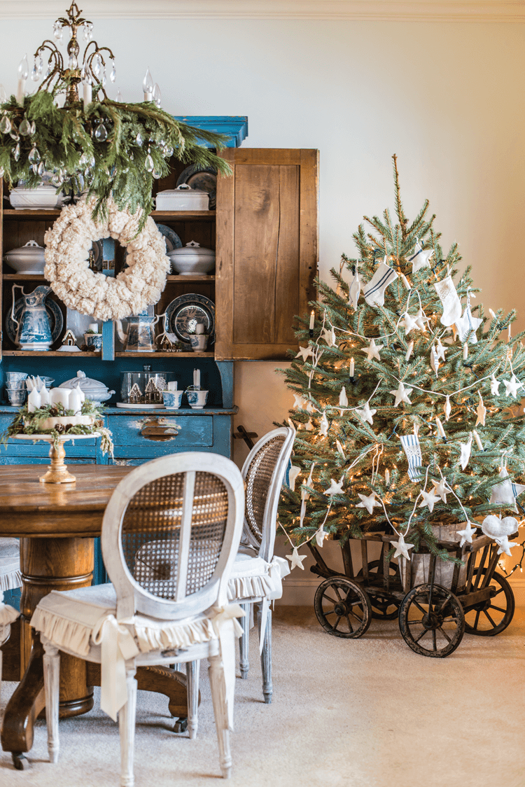 Fresh greenery hangs from the chandelier in Miss Mustard Seed's dining room. The Blue painted hutch features a yarn pom-pom wreath and the petite Christmas tree is placed nearby in an antique wooden wagon.