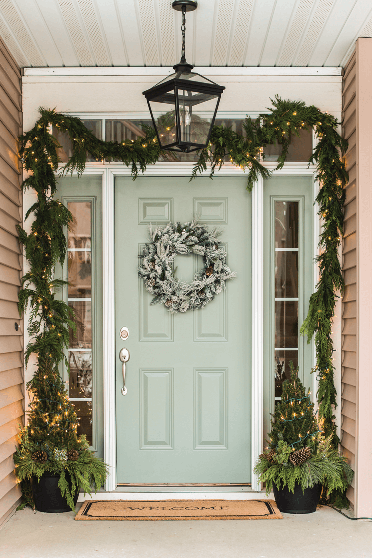 Fresh greenery in the form of natural garland, frosted wreath and topiaries create a welcoming winter scene on Miss Mustard Seed's front door.