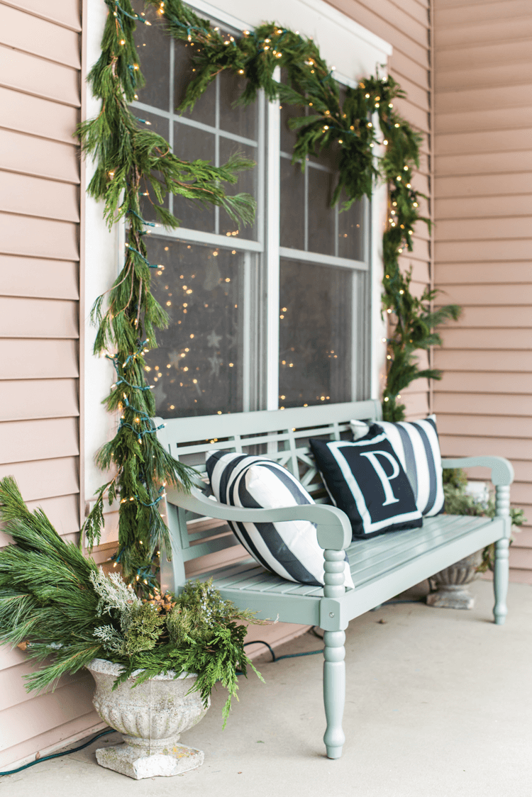 A blue painted bench creates a welcoming winter scene on Marian Parson's front porch. Fresh greenery strung with lights completes the look.