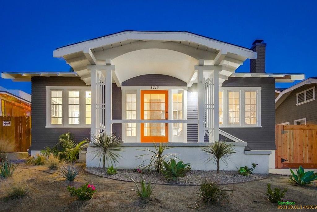 Exterior of a dark gray San Diego cottage with orange door