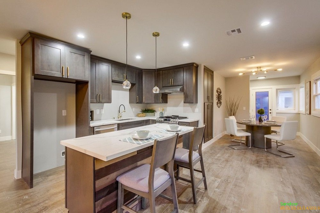 Newly renovated kitchen with brown cabinets, trendy lighting fixtures, and dining area.
