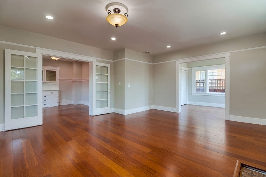 Spacious living room of a San Diego cottage with laminate hardwood floors.