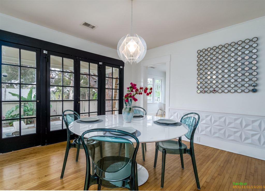 Trendy San Diego dining room with round white table, transparent turquoise chairs, and trendy chandelier.