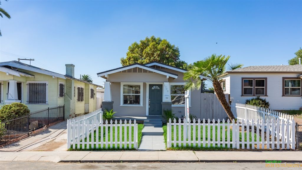 Adorable San Diego cottage with bright green front yard, white picket fencing, and slanted palm tree.