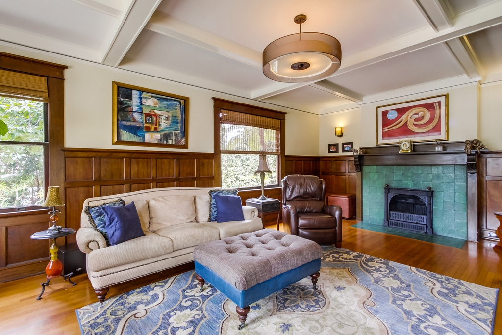 Charming living room of a historic San Diego home with vibrant green fireplace and retro chandelier.