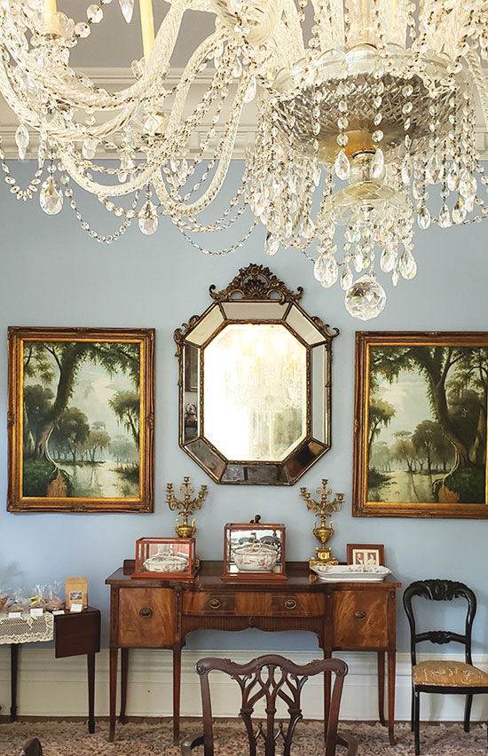 crystal chandelier above antique paintings and an elegant sideboard