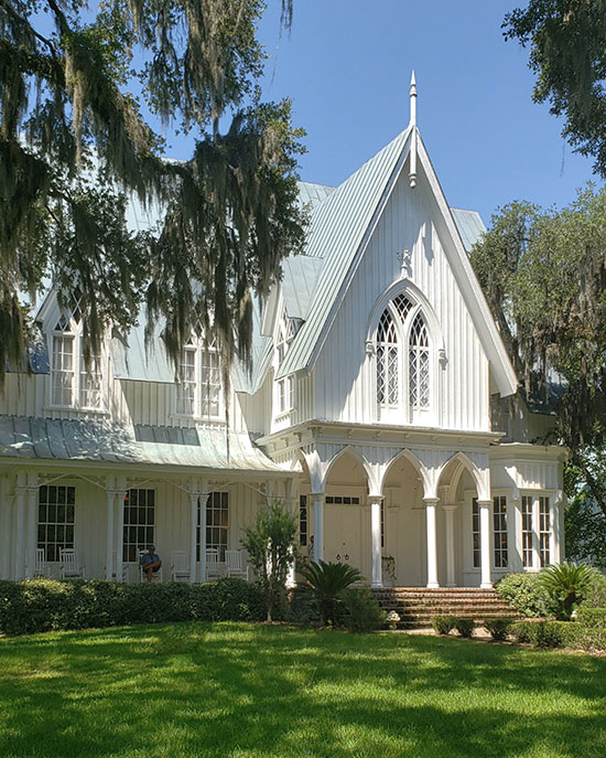 white gothic manor framed by trees