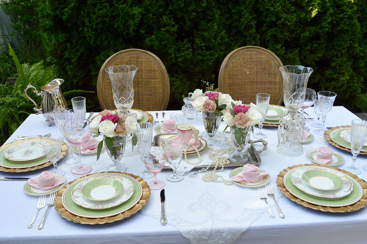 romantic table setting with gold cane chairs, roses and limoge china