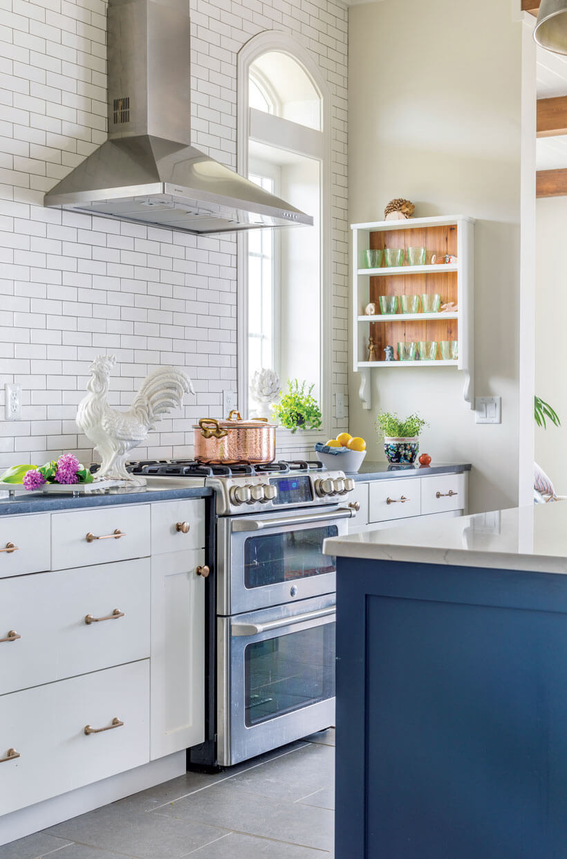A white kitchen with a blue island and subway-tile backsplash.