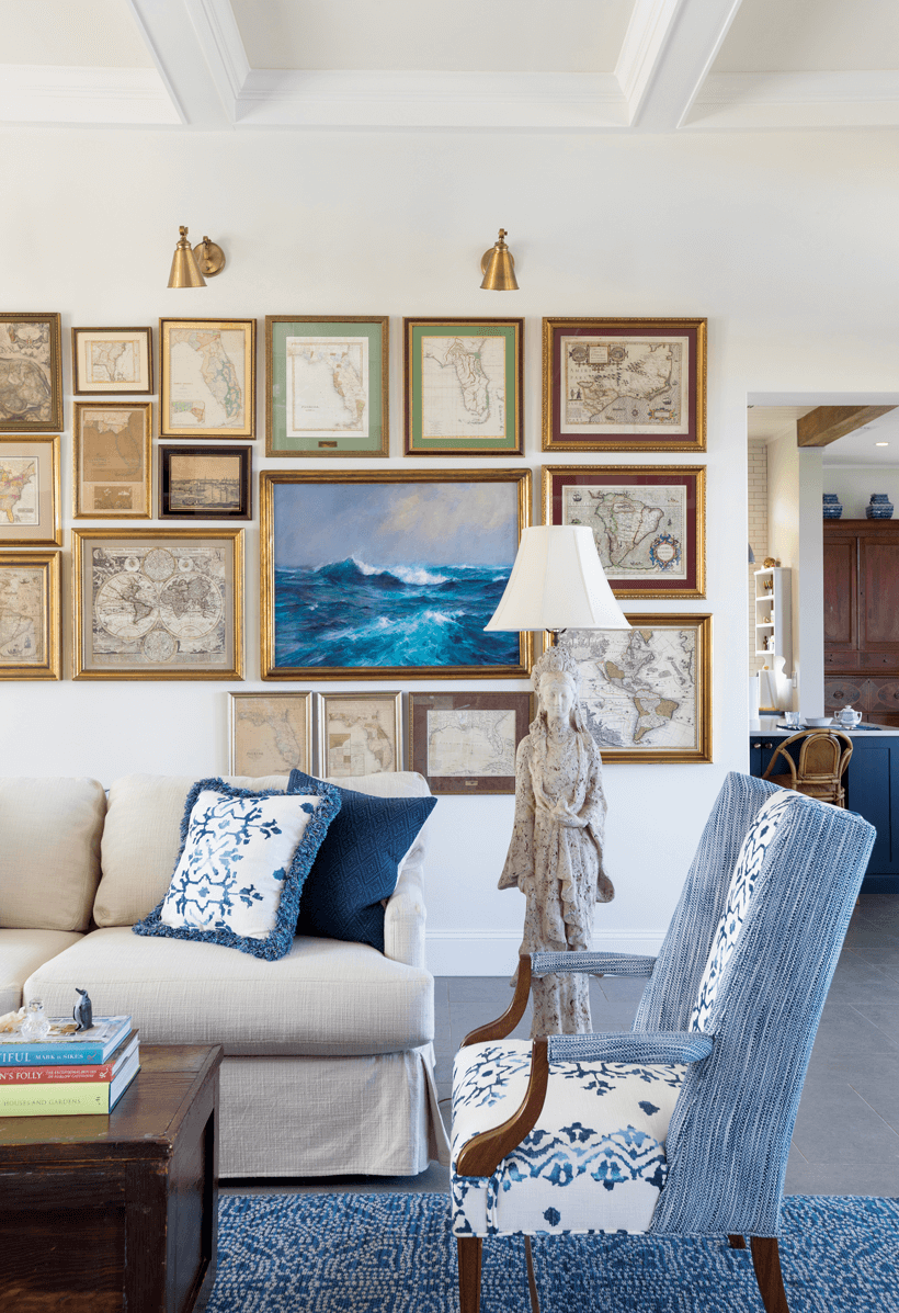 A living room with a gallery wall, blue and white chairs and pillows, and a unique lamp.